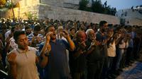 Des palestiniens musulmans prient devant la porte des Lions, à Jérusalem, le 27 juillet 2017 [AHMAD GHARABLI / AFP]