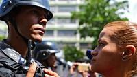 Une partisane du président autoproclamé vénézuelien Juan Guaido fait face à un policier lors d'une manifestation à Caracas le 9 mars 2019 [RONALDO SCHEMIDT / AFP]