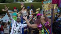 """Des danseurs lèvent les bras au ciel au sein du cortège """"Loucura suburbana"""", pendant le carnaval de Rio, le 8 février 2018 [MAURO PIMENTEL / AFP]"""