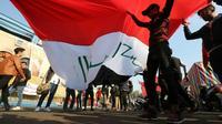 Des manifestants irakiens soulèvent un drapeau sur la place Tahrir à Bagdad, le 22 décembre 2019 [SABAH ARAR / AFP]