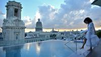 Une touriste au bord de la piscine sur le toit de l'hôtel Gran Manzana Hotel à La Havane, le 11 février 2019 [Yamil LAGE / AFP]