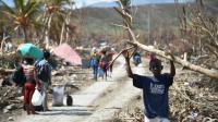 Des Haïtiens dans une rue dévastée après le passage de l'ouragan Matthew le 10 octobre 2016 à Les Cayes [HECTOR RETAMAL / AFP]