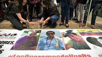 Des proches des deux journalistes équatoriens Javier Ortega et Paul Rivas et de leur chauffeur Efrain Segarra, allument des bougies près de leurs portraits après l'annonce de leur mort, le 13 avril 2018 à Quito [RODRIGO BUENDIA / AFP]