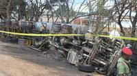 Un membre des forces de sécurité tanzanienne surveille la carcasse d'un camion-citerne accidenté, dont l'explosion a fait plus de 60 morts parmi les passants qui tentaient de le siphonner, le 10 août 2019, à Morogoro.  [STRINGER / AFP]