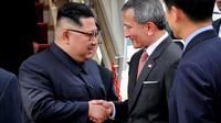 Photo fournie par le ministère de l'Information du leader nord-coréen Kim Jong Un (g) accueilli par le minitre singapourien des Affaires étrangères Vivian Balakrishnan à son arrivée à l'aéroport de Singapour le 10 juin 2018  [Terence TAN / Ministry of Communications and Information of Singapore/AFP]