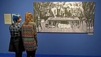 Des visiteurs d'une exposition en Pologne consacrée à Frida Kahlo et son époux contemplent une photo d'une toile disparue depuis plus d'un demi-siècle de l'artiste mexicaine, La table blessée, le 28 novembre 2017 à Poznan [JANEK SKARZYNSKI / AFP]