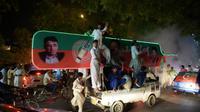 Des partisans de l'ancien champion de cricket Imran Khan, chef du Pakistan Tehreek-e-Insaf (PTI) manifestent leur joie dans une rue d'Islamabad le 25 juillet 2018 [AAMIR QURESHI / AFP]