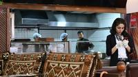 Une serveuse afghane consulte son téléphone dans le restaurant Afghan Kebab à Esenyurt, un distrcit d'Istanbul le 11 avril 2019 [OZAN KOSE / AFP]