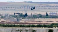 Un drapeau du groupe Etat islamique aperçu près de la frontière entre la Turquie et la Syrie, le 7 mai 2016 [ILYAS AKENGIN / AFP/Archives]