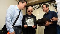 La femme du dissident chinois Liu Xiaobo, Liu Xia (centre) et son frère, Liu Xiaoguang (L), reçoivent les cendres du défunt après son incinération dans la ville de Shenyang, le 15 juillet 2015. [Handout / Shenyang Municipal Information Office/AFP]
