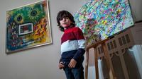 L'artiste allemand de 7 ans Mikail Akar pose devant ses peintures «Champi» et «Homme tournesol» avant l'ouverture de son exposition «Manus 11» à Berlin, le 13 décembre 2019.