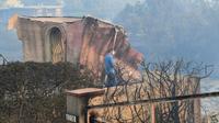 Un membre des services du sheriff du comté de Los Angeles marche au milieu de propriétés dévastées par les flammes à Malibu, en Califonrie, le 10 novembre 2018. [Robyn Beck / AFP]