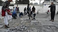 Des manifestants brisent des pavés à Alger tandis que la police fait usage de gaz lacrymogène, le 22 février 2019 [RYAD KRAMDI                         / AFP]