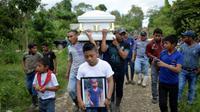 Un garçon porte une photo de Jakelin Caal, décédée aux Etats-Unis, pendant ses obsèques au Guatemala le 25 décembre 2018 [Johan ORDONEZ / AFP/Archives]