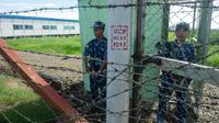 Des gardes armés à l'entrée du camp de transit de Nga Khu Ra pour les réfugiés rohingyas, le 28 juin 2018 à Maungdaw, dans l'Etat Rakhine, en Birmanie [- / AFP]