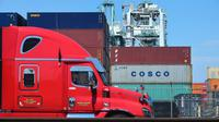 Un camion passe devant des conteneurs, dont l'un appartenant au groupe chinois Cosco, le 6 juillet 2018 dans le port de Long Beach, en Californie [Frederic J. BROWN / AFP/Archives]