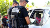 Des gendarmes contrôlent les identités des conducteurs le 15 mars 2018 à Majicavo à Mayotte [Ornella LAMBERTI / AFP]