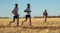 Deux marathoniens passent devant un soldat lors du premier marathon jamais organisé au Niger, le 29 décembre à Agadez. [Nora Schweitzer / AFP]