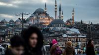 Des piétons traversent le pont de Galata à Istanbul, le 27 janvier 2018, avec la mosquée de Suleymaniye en arrière-plan [YASIN AKGUL / AFP/Archives]