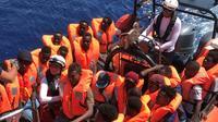 Des migrants secourus dans les eaux internationales au large de la Libye, à bord d'un bateau pneumatique appartenant au navire humanitaire Ocean Viking le 12 août 2019. L'Ocean Viking, affrété par SOS Méditerranée et Médecins sans frontières, a secouru lundi 105 migrants supplémentaires dans ces eaux, et compte désormais 356 personnes à bord. [Anne CHAON / AFP]