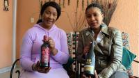 La fille ainée de Nelson Mandela, Makaziwe Mandela (g), avec sa fille Tukwini Mandela posent avec leurs bouteilles de vin, le 26 avril 2013 à Johannesburg [Jennifer Bruce / AFP/Archives]