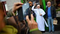 Des touristes se prennent en photo avec une statue de cire représentant le pape François à Dublin, le 24 août 2018 [Ben STANSALL / AFP]