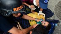 Des secouristes viennent en aide à une femme blessée lors des manifestations à Caracas le 20 avril 2017 [RONALDO SCHEMIDT / AFP]