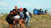 Un corps porté le 29 septembre 2018 par des habitants de Palu après un fort séisme sur l'île indonésienne des Célèbes. [MUHAMMAD RIFKI / AFP]