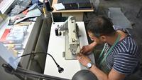 Penché sur sa machine à coudre, le Syrien Khaldoun Alhussain transforme un canot pneumatique en sac ou cabas, dans l'atelier de la petite entreprise mimycri à Berlin [Tobias SCHWARZ / AFP]