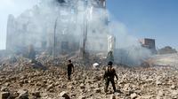 Des rebelles Houthis inspectent les dégâts, le 5 décembre 2017, après une frappe aérienne attribuée à la coalition militaire menée par Ryad contre le palais présidentiel à Sanaa,  [Mohammed HUWAIS / AFP/Archives]