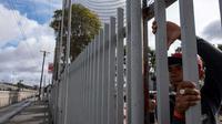 Des migrants d'Amérique centrale espérant pouvoir se rendre aux Etats-Unis regardent à travers les grilles d'un refuge situé près de la fontière américano-mexicaine, à Tijuana au Mexique, le 22 novembre 2018 [Guillermo Arias / AFP]