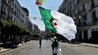 Un Algérien agite le drapeau national lors d'une manifestation à Alger contre le pouvoir, le 26 juillet 2019 [RYAD KRAMDI                         / AFP]
