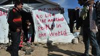 Des migrants dans le camp d'Idomeni en Grèce, le 26 mars 2016, à proximité de la frontière avec la Macédoine [SAKIS MITROLIDIS / AFP]