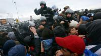 Des policiers face aux migrants qui affluent le 19 octobre 2015 à Trnovec à la frontière de la Slovénie et de la Croatie [STR / AFP]