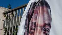 Un homme accroche un portrait du président zimbabwéen Emmerson Mnangagwa avant la cérémonie marquant son investiture à Harare le 26 août 2018 [Jekesai NJIKIZANA / AFP]