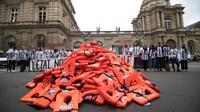Un collectif de bénévoles d'aide aux migrants a déversé des gilets de sauvetage devant le Sénat pour alerter sur les naufrages en mer et protester contre le projet de loi asile-immigration, le 19 juin 2018 à Paris [Eric Feferberg / AFP]