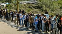 """Des migrants font la queue pour recevoir des rations alimentaires de l'ONG """"L'Auberge des Migrants"""" à l'entrée de la Nouvelle Jungle à Calais le 8 août 2015  [Philippe Huguen / AFP]"""