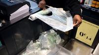 Un employé de supermarché prend un sac plastique à usage unique à Paris, le 28 décembre 2015 [STEPHANE DE SAKUTIN / AFP/Archives]