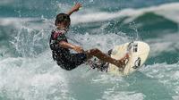 Rickson Falcao, 10 ans, surfe sur une vague au large de Saquarema, dans l'Etat de Rio, au Brésil, le 29 novembre 2017 [LEO CORREA / AFP]