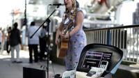 La chanteuse de rue Charlotte Campbell utilise un lecteur de carte bancaire sans contact pour récolter des dons, au pied du London Eye (grande roue) à Londres le 1er septembre 2018 [Daniel LEAL-OLIVAS / AFP]