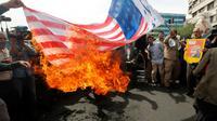 Des Iraniens brûlent un drapeau américain lors d'une manifestation à Téhéran après le retrait des Etats-Unis de l'accord nucléaire, le 11 mai 2018 [STRINGER / AFP]