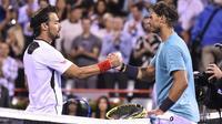 L'Espagnol Rafael Nadal (d) serre la main de l'Italien Fabio Fognini après l'avoir battu en quarts de finale du tournoi Masters 1000 de Montréal, le 9 août 2019 [Minas Panagiotakis / Getty/AFP]