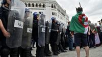 Un manifestant algérien fait face aux forces anti-émeutes à Alger, le 24 mai 2019 [RYAD KRAMDI                         / AFP]