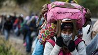 Une migrante vénézuelienne marche le long de la route à proximité de Tulcan, en Equateur, le 21 août 2018 [Luis ROBAYO / AFP]