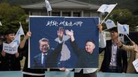 Les photos du président sud-coréen Moon Jae-in (g) et du leader nord-coréen Kim Jong-Un lors d'un rassemblement pour la paix, le 26 avril 2018 à Séoul [Ed JONES / AFP]