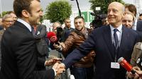 Le Président Emmanuel Macron, alors ministre de l'Économie, serre la main du maire de Bordeaux, Alain Juppé, à Villepinte, près de Paris, le 16 juin 2016 [PATRICK KOVARIK / AFP/Archives]