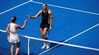 La N.1 mondiale Simona Halep (de dos) salue la victoire de son adversaire, l'Estonienne Kaia Kanepi au premier tour de l'US Open, le 27 août 2018 à Flushing Meadows [Eduardo MUNOZ ALVAREZ / AFP]