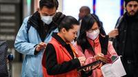 Une employée aide des voyageurs en provenance de Chine le 26 janvier 2020 à l'aéroport de Roissy  [Alain JOCARD / AFP]