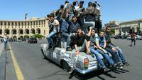 De jeunes Arméniens partisans de l'opposition défilent sur une voiture dans Erevan le jeudi 26 avril 2018 [Vano SHLAMOV / AFP]