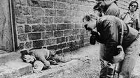 Des journalistes photographient et filment les cadavres d'un homme et de son bébé, le 20 mars 1988, dans la ville kurde de Halabja, après l'attaque de l'armée irakienne [IRNA / AFP/Archives]